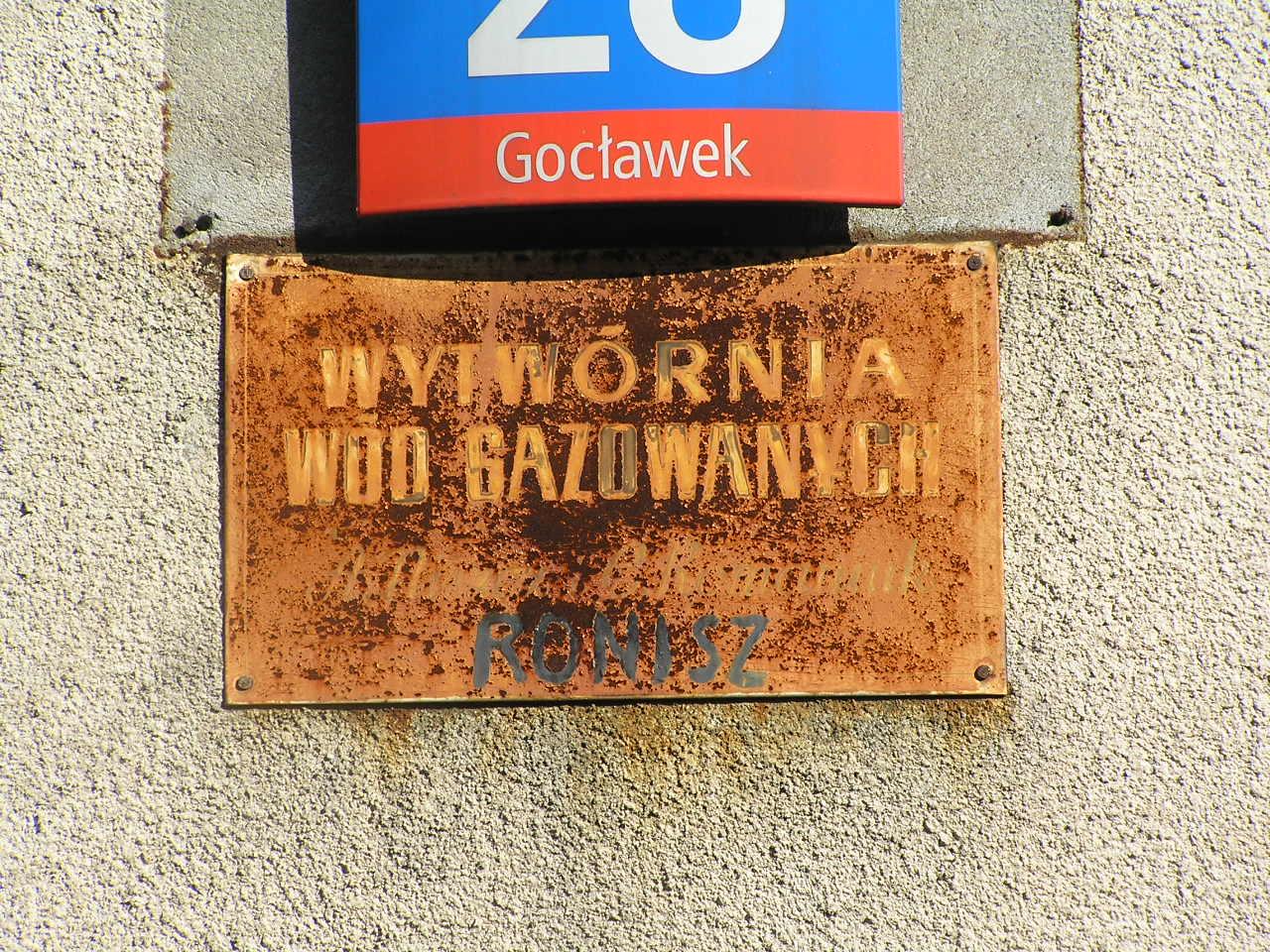 Tabliczka z nazwą firmy umieszczona na budynku przy ulicy Podolskiej 28 na Grochowie