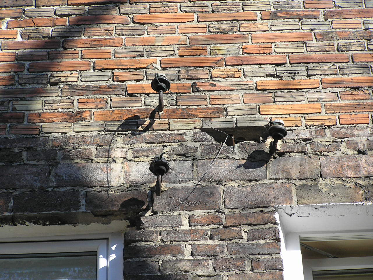 Izolatory na ścianie kamienicy przy ulicy Rębkowskiej 4 na Grochowie