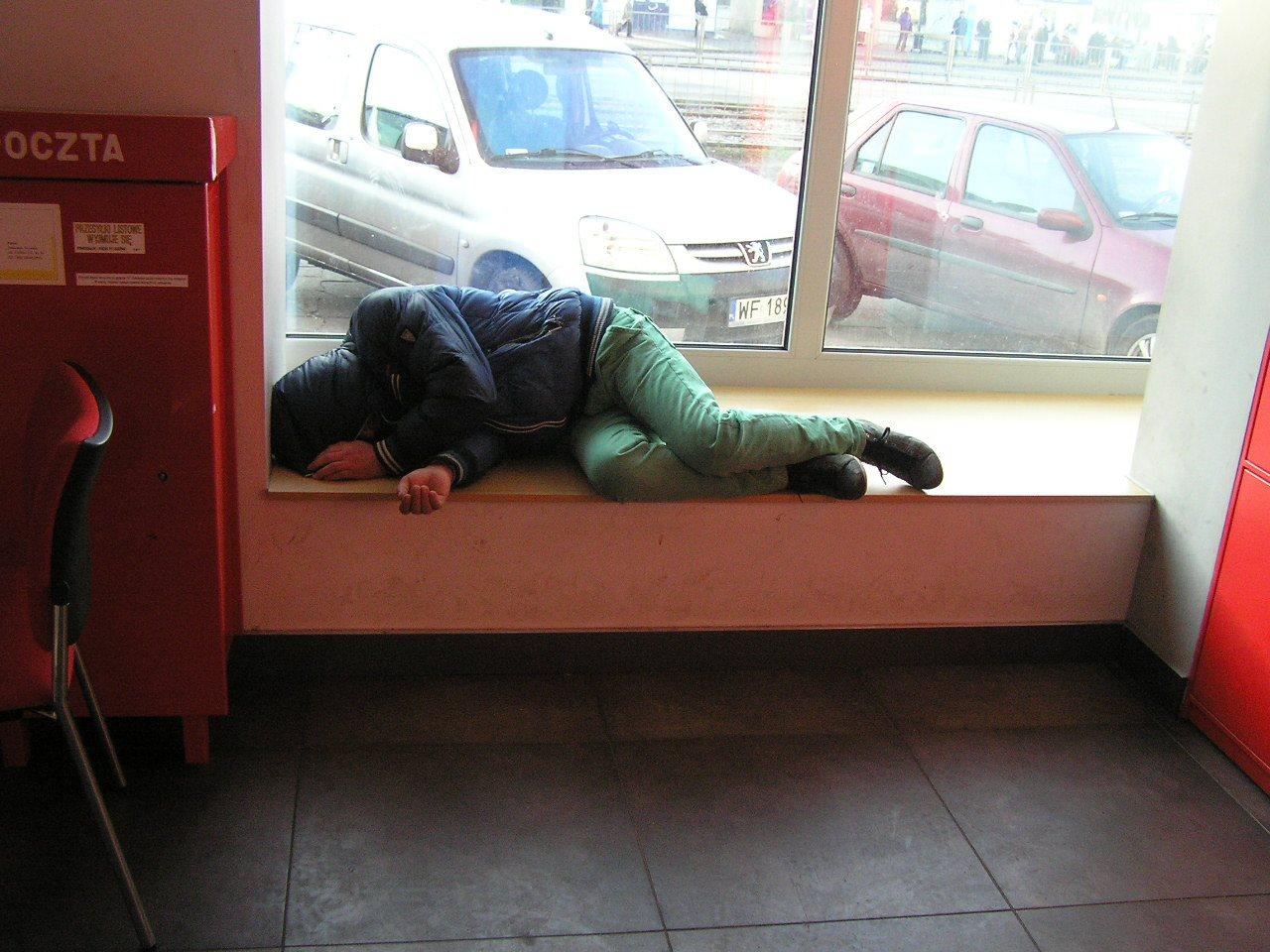 Bezdomni śpią na poczcie.